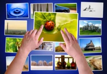 Hands choosing photos on virtual desktop