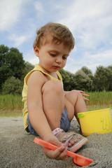 bambina paletta secchiello sabbia giocare