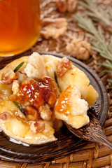 Cheese baked with honey, nuts and herbs