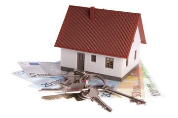 kleines Haus mit Geldscheinen und Wohnungsschlüssel