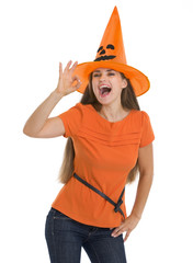 Happy young woman in Halloween hat showing ok gesture