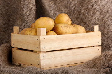 Ripe potatoes in wooden box on sacking