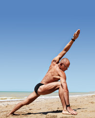 Athletic build young man doing wide angle yoga pose
