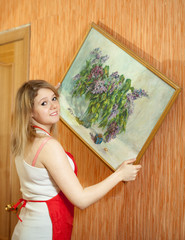 woman  hangs the art picture on wall
