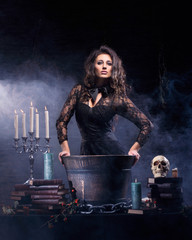 A young and sexy brunette witch making poison in a pot
