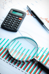 Calculator and magnifier on business graph.