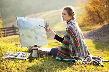 Young artist painting a landscape
