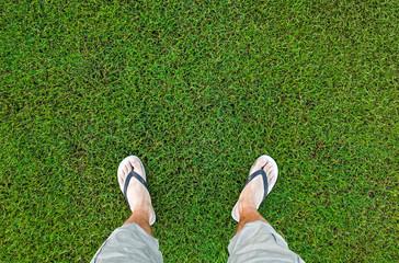 Feet of the man standing on fresh green grass
