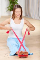frau trainiert mit einem pilates-band zu hause
