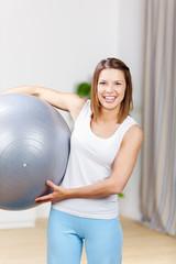 lachende frau trägt gymnastikball