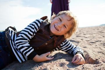 Smiling boy lying on the beach.