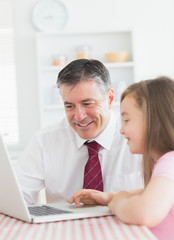 Daughter and father using laptop together
