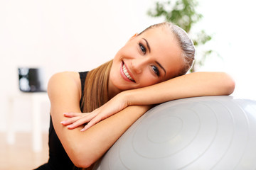 Happy and beautiful woman with fitness ball at home