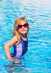 blond kid girl in blue pool posing with sunglasses
