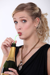 Woman drinking champagne from a straw
