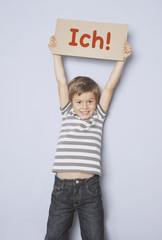 Selbstbewusster Junge hält ein Schild hoch