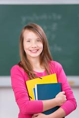 lächelnde schülerin mit unterlagen im klassenzimmer