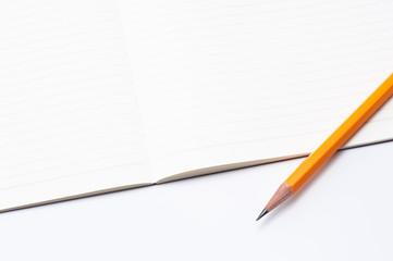 開いた白紙のノートと鉛筆のアップ