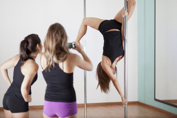 Taking photos from instructor at pole fitness class