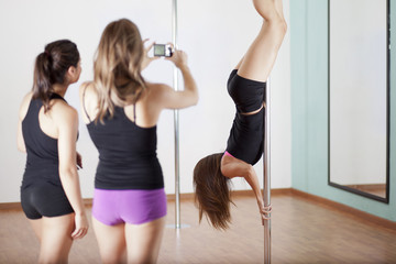 Pole fitness instructor and students during a demonstration