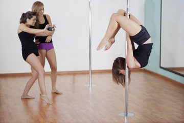 Pole fitness students and instructor during a demonstration