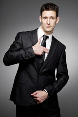 Businessman in black suit making gun gesture.