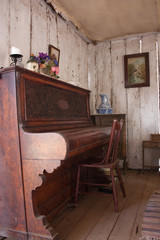 Vintage piano in old wooden cottage