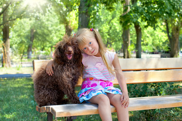 Little girl hugging a poodle dog in the park