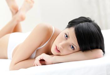 Woman in underwear is lying in the queensize bed