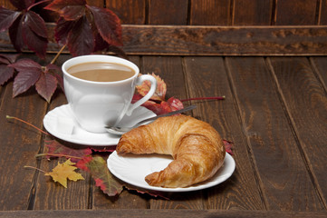 a croissant and a cup of coffeee with milk on a old wooden table