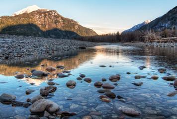 Fotomurales - River Leading Towards Sunset Lit Mountains