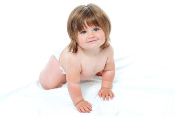Charming toddler in diapers trying to crawl