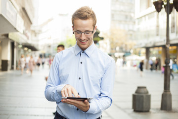 Happy Smiling Businessman With Tablet Computer in public space