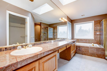 Large luxury bathroom with red granite countertops and tub.