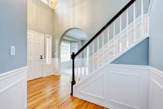 Blue empty entrace with white molding and staircase.