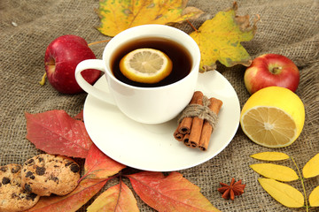 cup of hot tea and autumn leaves, on burlap background