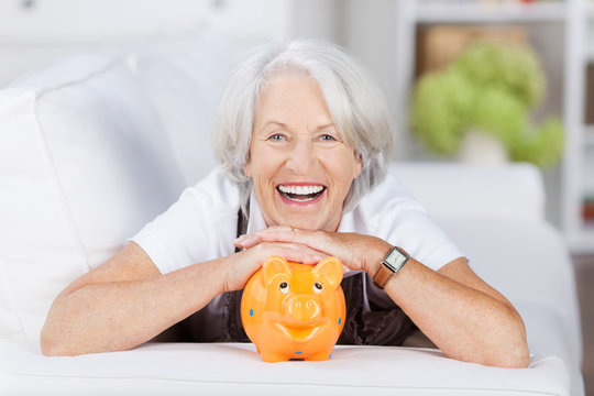 lachende seniorin mit ihrem sparschwein