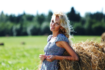 girl next to a stack of hay