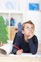 junge schreibt wunschzettel an das christkind