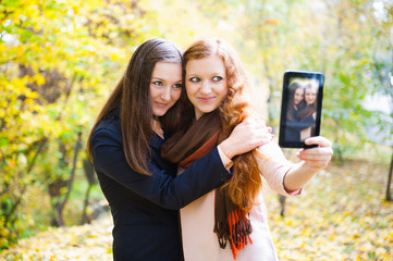 Two girls taking self portrait in autumn park