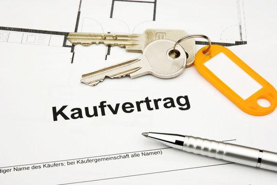 Kaufvertrag mit Schlüssel, Kuli und orangem Anhänger