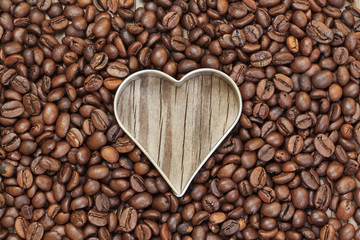 Heart shape in coffee beans on a wooden texture.