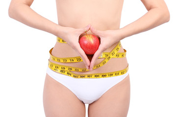 woman's waist with measuring tape holding red apple
