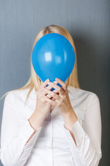 frau mit luftballon vor grauer wand