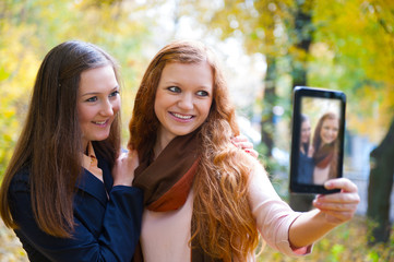 Two girls taking picture with digital tablet