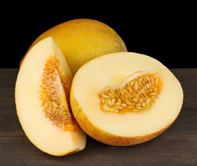 Cut ripe melons on wooden table on black background