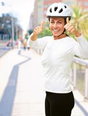 Woman wearing helmet showing thumb up