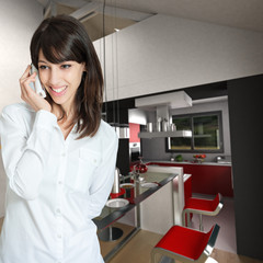 Young woman phoning at home, by the kitchen