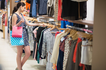 Woman searching through clothes holding two bags