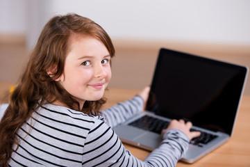 lächelndes mädchen tippt auf dem laptop